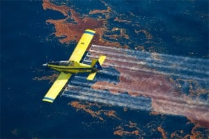 Plane spraying dispersants on an oil spill.